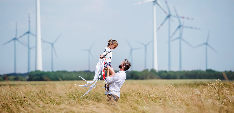 Vater mit kleiner Tochter auf dem Feld vor einem Windpark