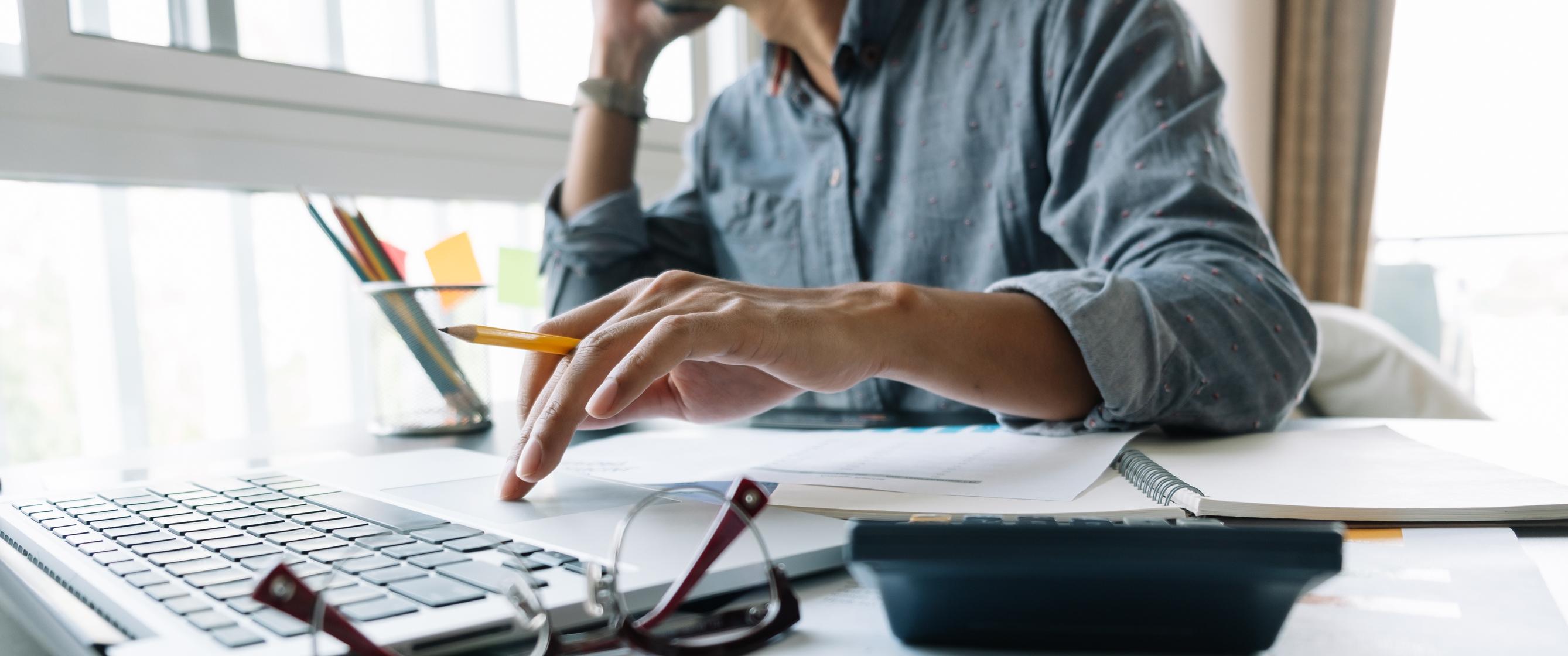 Person telefoniert am Schreibtisch bei der Prüfung von Unterlagen