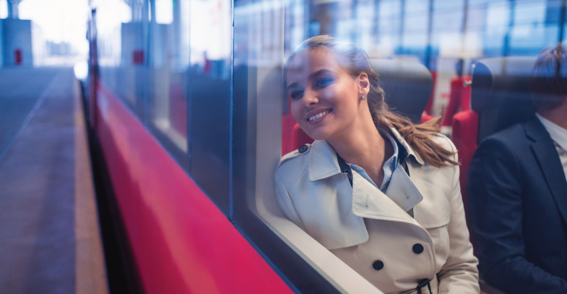A woman happily looking outside through the window of a train
