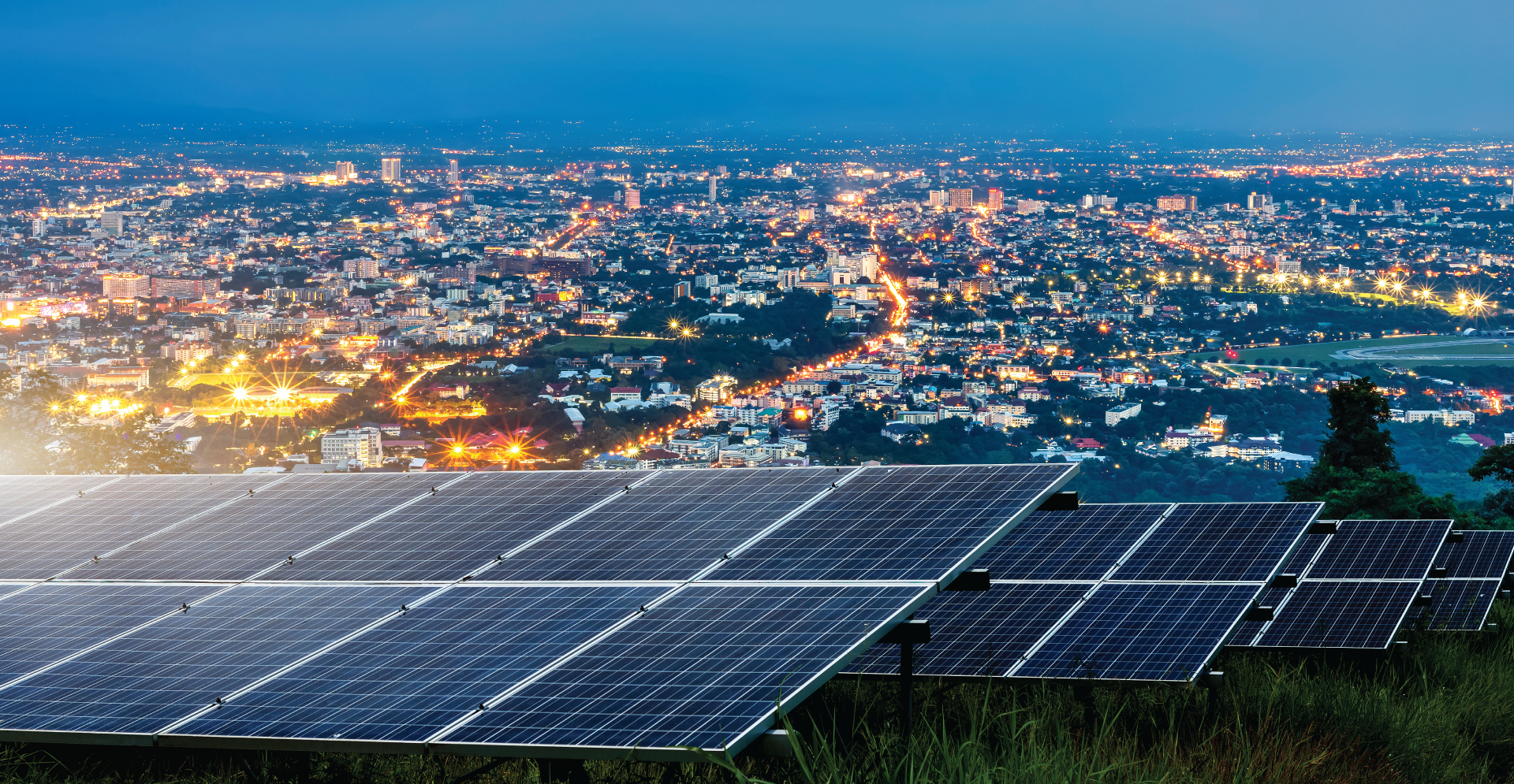 Solar panels on mountain top with overlooking city night lights