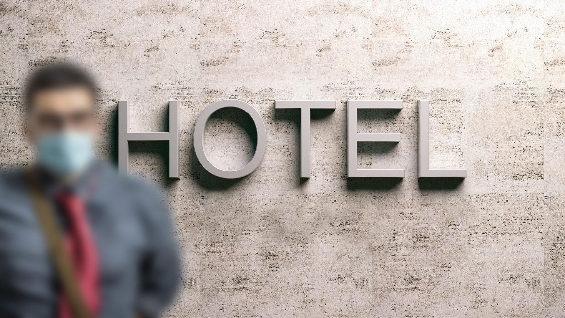 Mann mit medizinischer Mund-Nasen-Bedeckung in Hotel-Lobby