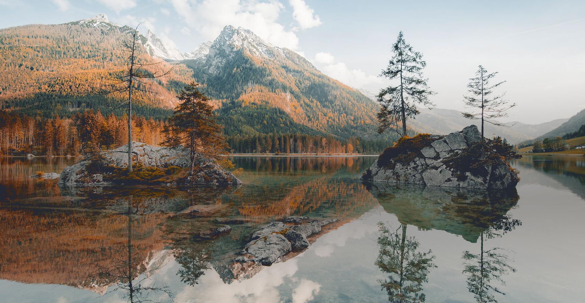 Gebirgssee mit Bergen und Wäldern im Hintergrund