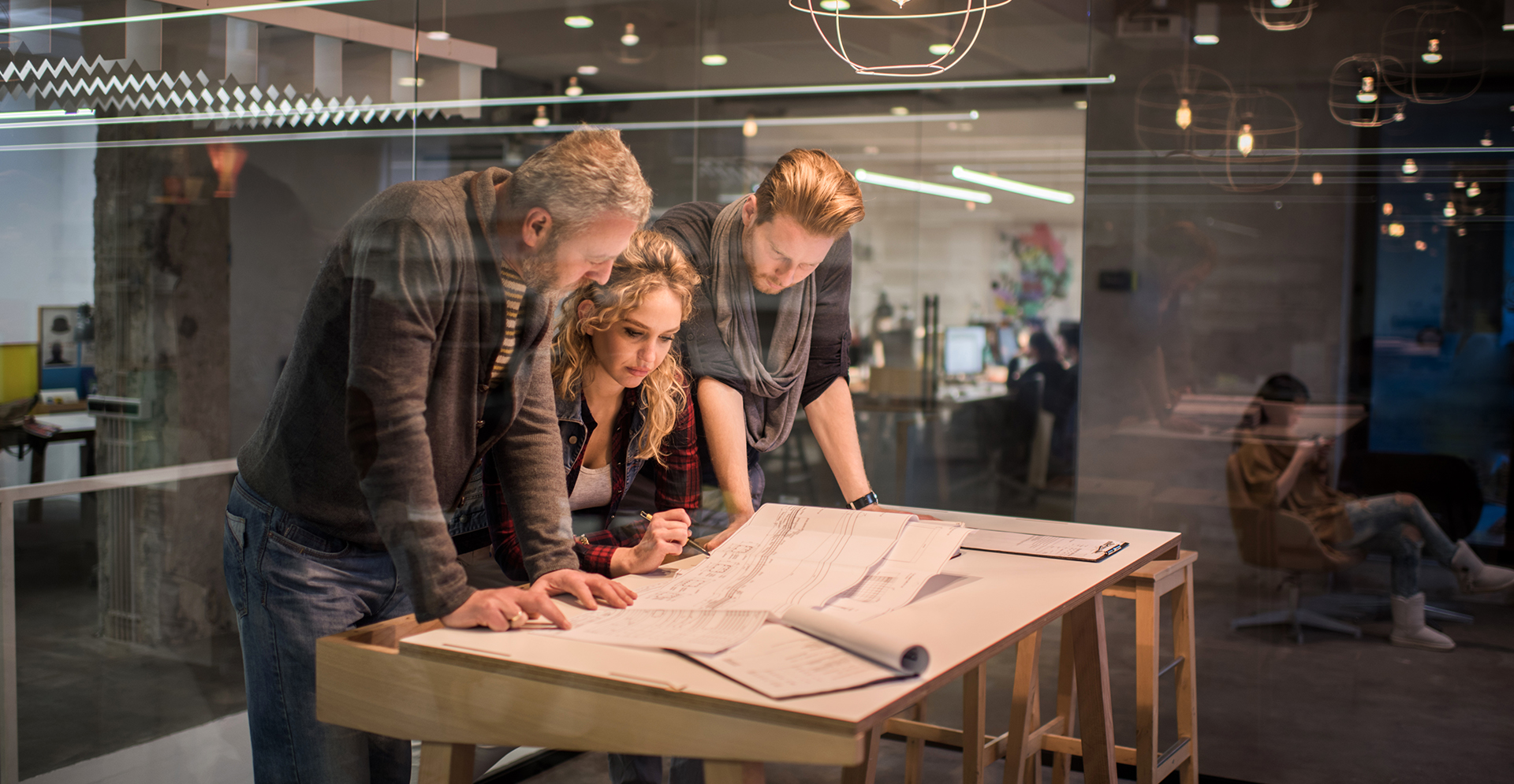 Team van Arcadis Architecten gebogen over een tafel kijkend naar een ontwerp.