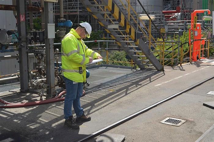Mann in Schutzausrüstung führt Prüfung durch auf einer Baustelle