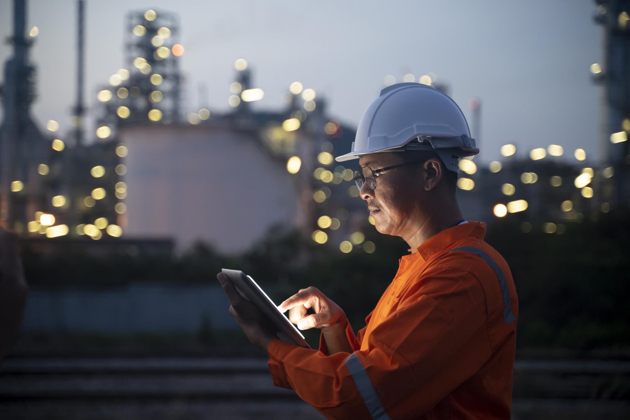 Ingenieur mit Tablet in der Nähe von Ölraffinerie in der Dämmerung