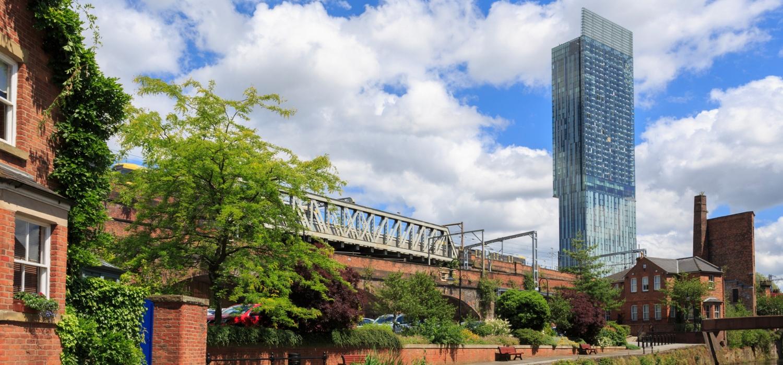 Gebouw met groene omgeving en op de achtergrond een hoge toren van een kantoor.