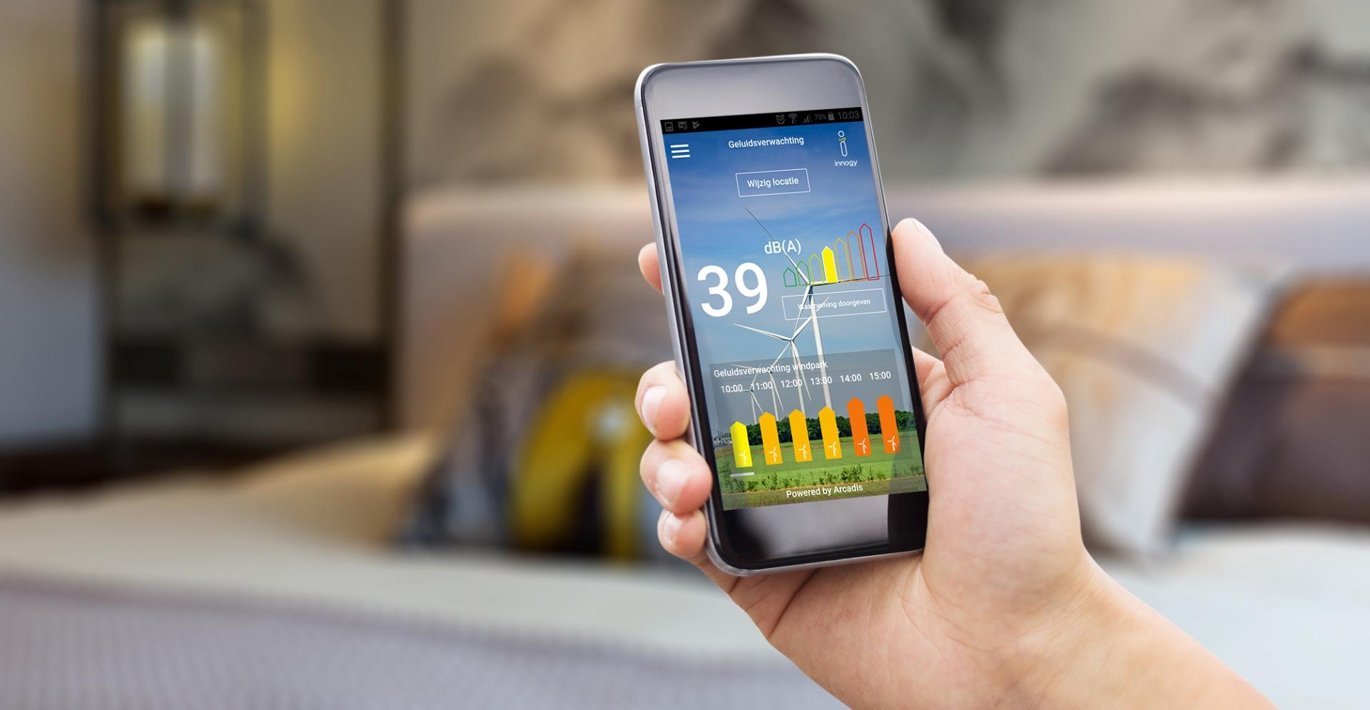 Iemand die een smartphone vasthoudt met daarop een app over windverwachting bij windturbines