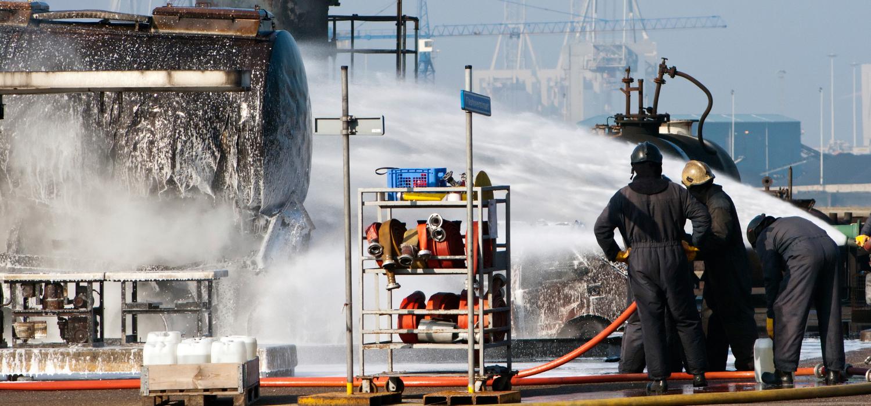 Brandweerlieden bezig met  het blussen van een tank met blusschuim