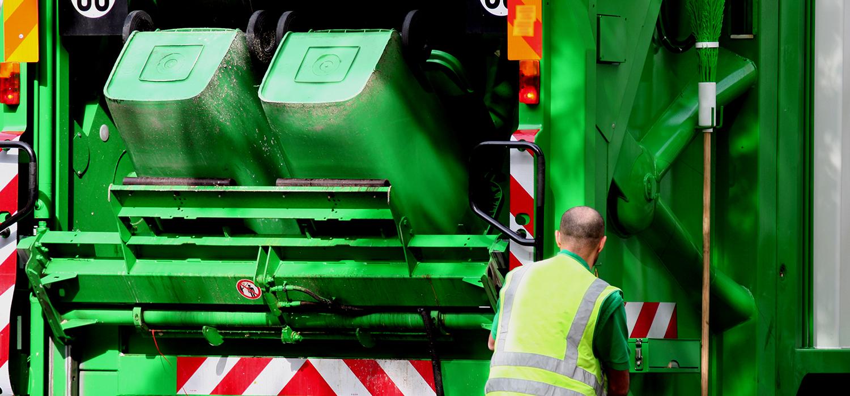 Groencontainers die achterin de vuilniswagen worden geledigd door medewerker van de vuilnisophaaldienst.