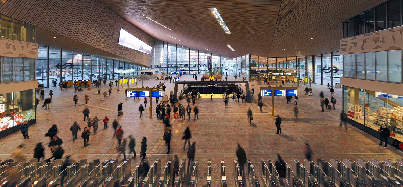 Ontvangsthal van centraal station Rotterdam met OV poortjes en reizigers die komen en gaan